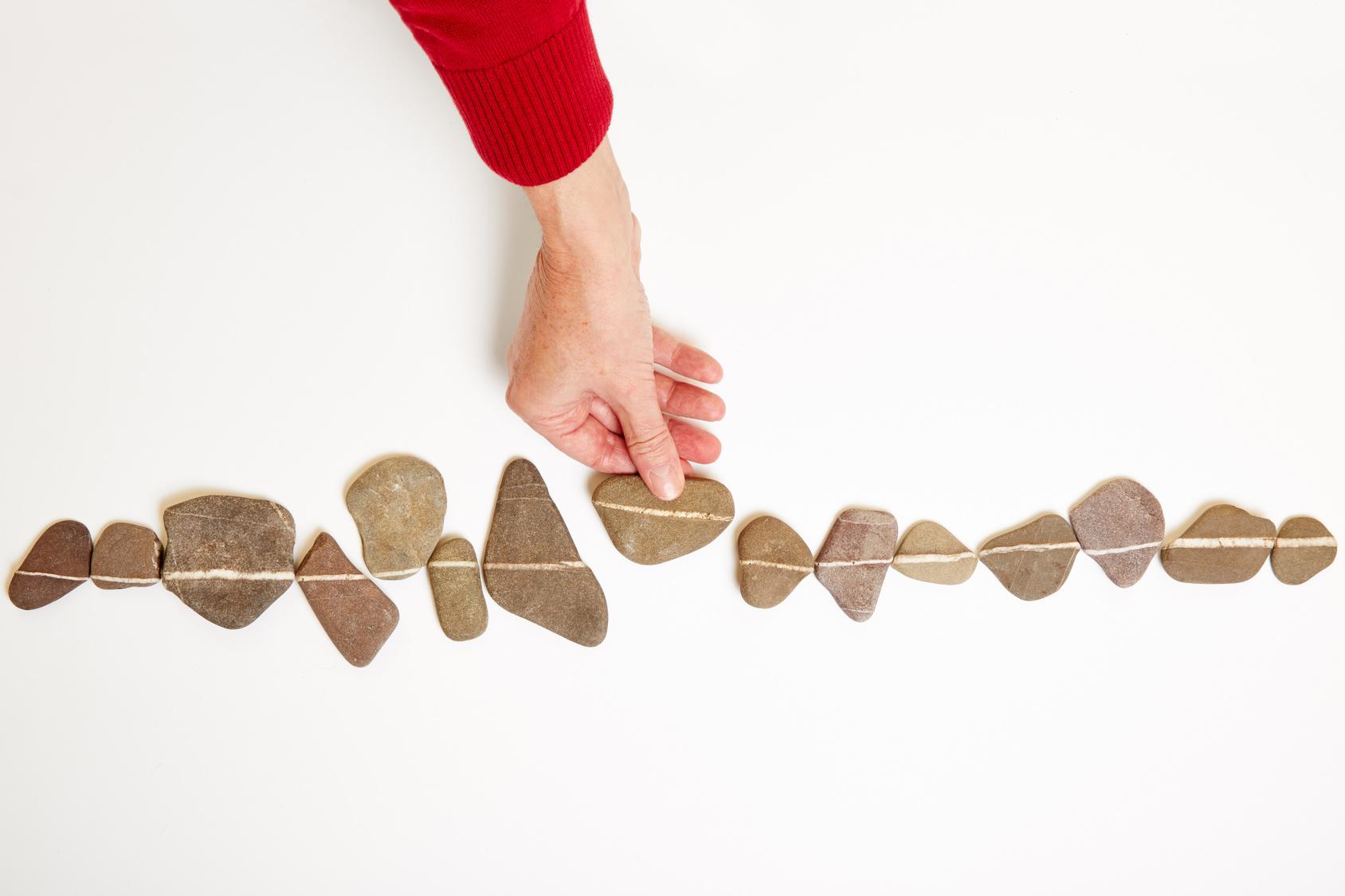 Hand schiebt Stein in eine Linie aus vielen anderen Steinen